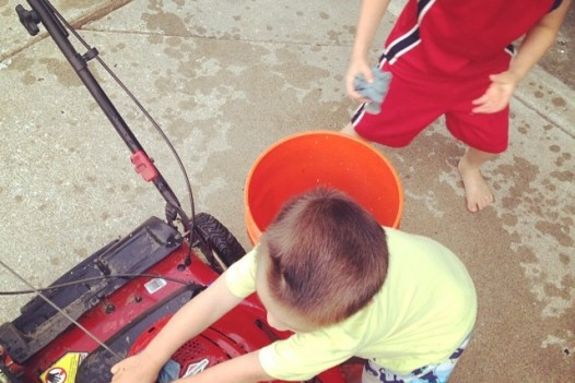 "When asked to smile, he responded, ""We can't do a picture right now Daddy, we're cleaning your mower for you."" Thus, an action shot."